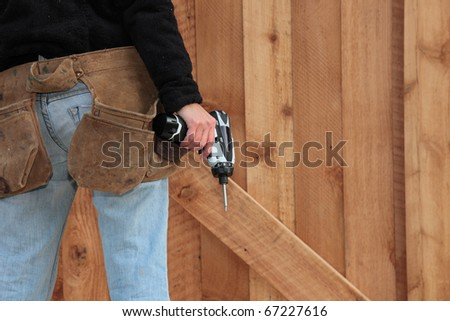 A carpenter stands in front of a wooden door she has just finished building. - stock photo