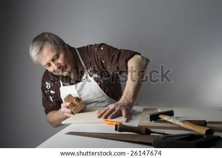 a carpenter using an hand plane - stock photo