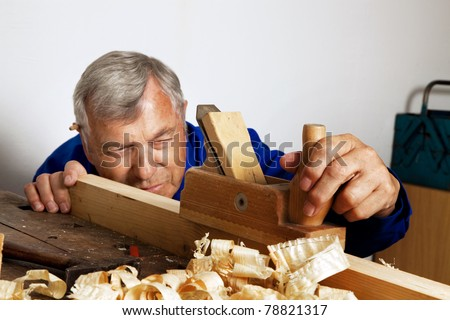 A carpenter with a planer and wood shavings in the workshop. - stock photo