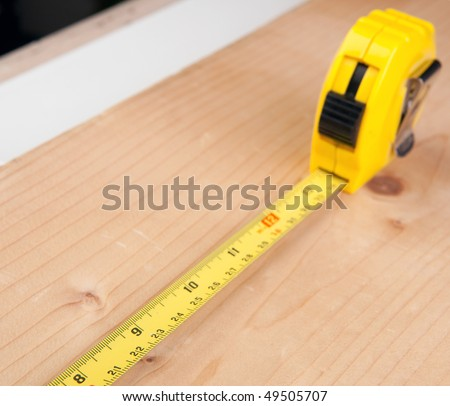 A carpenters steel flexible rule on a piece of wood - stock photo