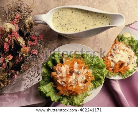 a carrot salad served in a white plate, with his dressing  beside in a serving pot, some pink and white dried flower beside shot in studio on a pink satin and marble background - stock photo