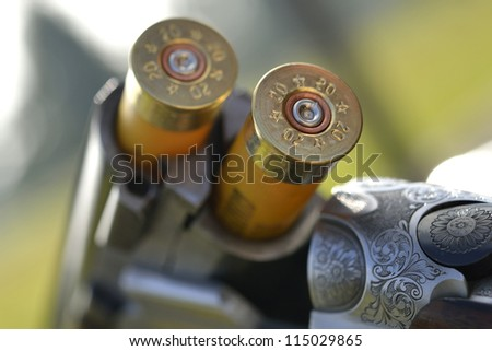 A cartridge loaded and ready in an under and over 12 bore shotgun - stock photo