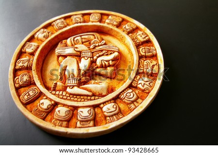 A carved Mayan calendar on dark background - stock photo