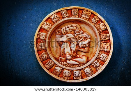 A carved Mayan calendar on textured background - stock photo