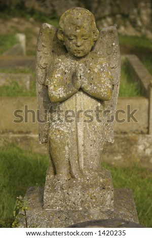 A carved praying angel headstone covered in moss - stock photo