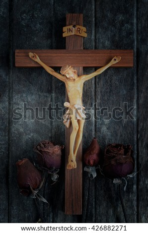 A carved statue of the Crucifixion of Jesus Christ with dried roses on wood background  - stock photo