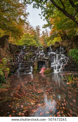 A cascade in Virginia Water in the fall colors, Surrey, UK - slow shutter speed effect