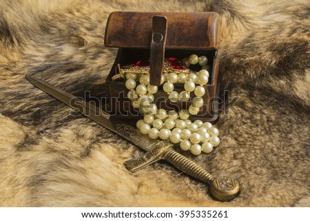 a casket and dagger with jewels on natural fur a wild Wolf dagger and casket - stock photo