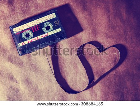 a cassette tape pulled out in the shape of a heart with a long shadow toned with a retro vintage instagram filter app or action effect on a brown paper textured background - stock photo