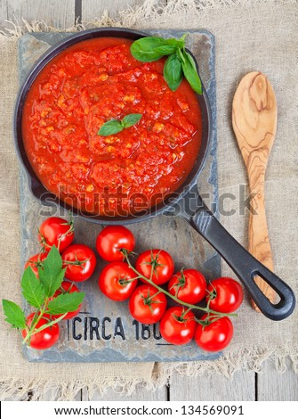 A cast iron pan filled with tomato sauce made from organic, heirloom tomatoes, resting on a piece of vintage salvaged slate, circa 1804.