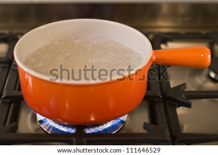A cast iron pan of boiling water on a modern gas range cooker - stock photo