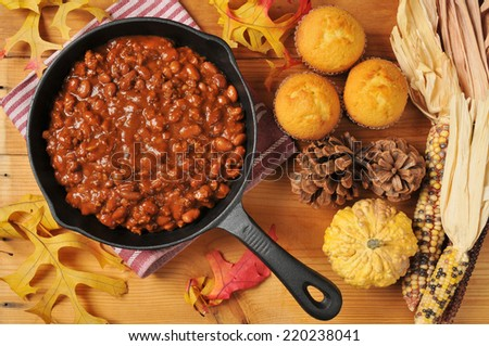 A cast iron skillet of chili con carne with cornbread muffins, shot from a high angle view - stock photo