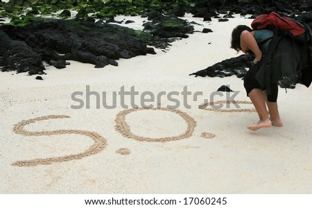 A castaway write a SOS message in the sands in hope of rescue - stock photo