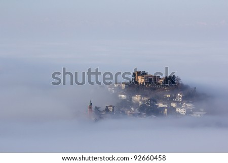 A castle above the clouds. Italy, Oltrepo Pavese, Mornico Losana. A village with castle that emerges from the fog. - stock photo