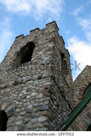 A castle-like turret rising out of a small chapel. - stock photo
