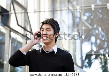 A casual asian businessman talking on the phone