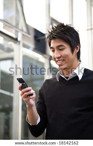 A casual asian businessman texting messages on his cellphone - stock photo