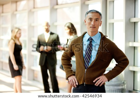 A casual Asian looking business man with colleagues in the background
