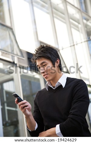 A casual asian man texting on his cellphone
