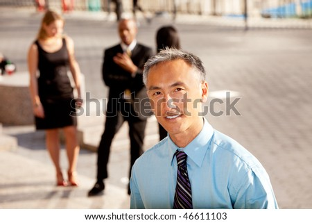 A casual business man with colleagues in the background - outdoor portrait - stock photo