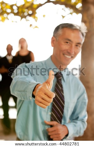A casual business man with thumbs up - stock photo