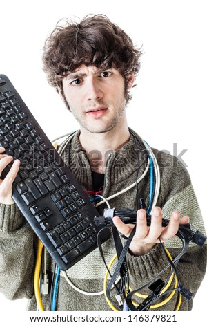 a casual guy with tangled cables and a keyboard struggeling to get computer assistance. isolated on white - stock photo