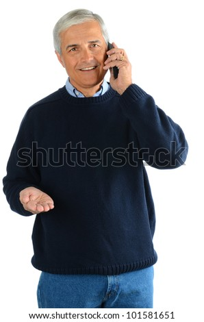 A casual middle aged Man in blue jeans and sweater talking on his cell phone and gesturing with his other hand. Vertical format over a white background. - stock photo