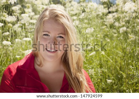 A casual portrait of a teen girl with blonde hair sitting amongst wildflowers on the side of the road. - stock photo