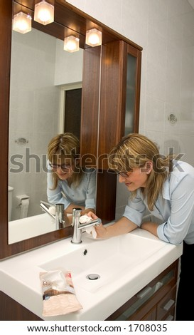 A casual women using a disinfectant wipe to clean the bathroom tap.