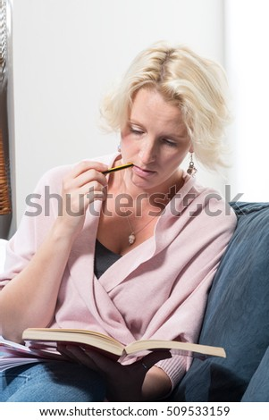 A casually dressed middle aged blonde woman sits on a sofa or couch holding a book and biting the end of a pencil in concentration. COPY SPACE