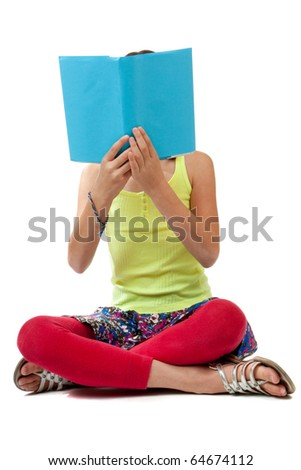 A casually dressed school age girl sits crossed legged and holds up a book with a blank blue cover up over her face. - stock photo