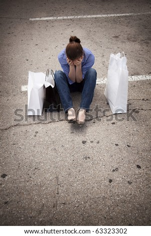A casually dressed young woman sitting in an empty parking lot with shopping bags and looking down as she covers her face.  Maybe she is feeling down because she spent more than she intended to.