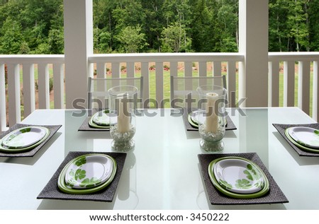 A casually sophisticated dining area on a patio porch of a home. - stock photo