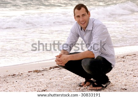A casually well dressed smiling young adult crouches at the water's edge at the beach. - stock photo