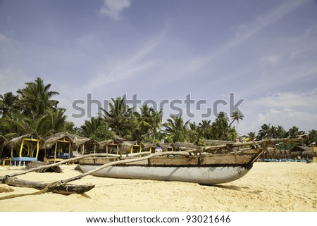 A catamaran lies at the Hikkaduwa Beach in Sri Lanka with brightly blue sky, slightly clouds and sunshine. In the background are deckchairs with palmleaf-roofing and coconut palms. - stock photo