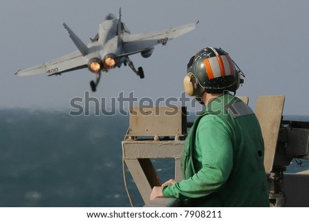A Catapult Crewman Watches an F/A-18C Hornet Launch From the Nuclear Aircraft Carrier, USS Enterprise - stock photo