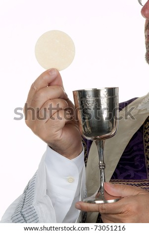 A Catholic priest with a chalice and host at Communion - stock photo