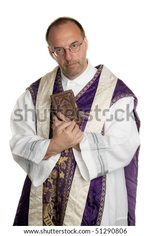 a Catholic priest with bible in worship - stock photo