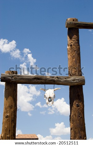 a cattle skull hangs from western wooden gate - stock photo