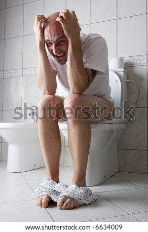 A caucasian adult man with frustrated expression while on toilet seat with his boxers around his ankles. Wearing white shirt and having his hands and fingers on his bald head. - stock photo