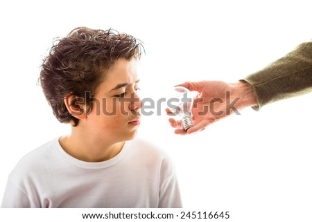 A Caucasian boy takes a puzzled look to real lightbulb that adult hand is giving to him from his left side - stock photo
