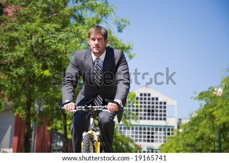 A caucasian businessman riding a bicycle to work, can be used for gas savings concept - stock photo