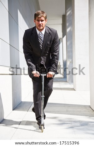 A caucasian businessman riding a scooter to work, can be used for green or gas savings concept - stock photo