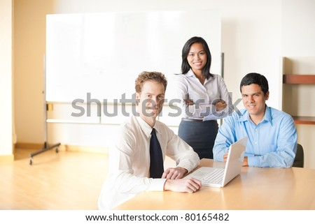 A Caucasian businessman with laptop leads a team meeting with his Hispanic and Asian coworkers in modern beige conference room with large blank whiteboard. Horizontal copy space