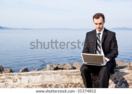 A caucasian businessman working on his laptop outdoor - stock photo