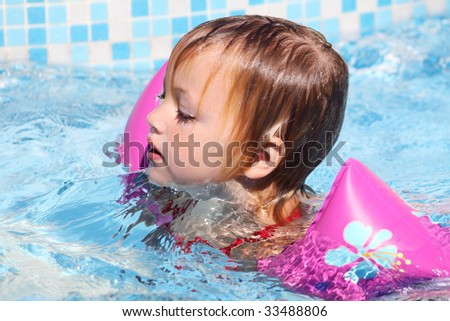 a caucasian child swimming for dry ground with armbands - stock photo