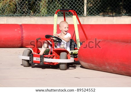 a caucasian child undergoing chemotherapy treatment due to cancer having fun on a go cart at a fun fair