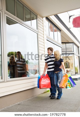 A caucasian couple carrying shopping bags on a shopping trip