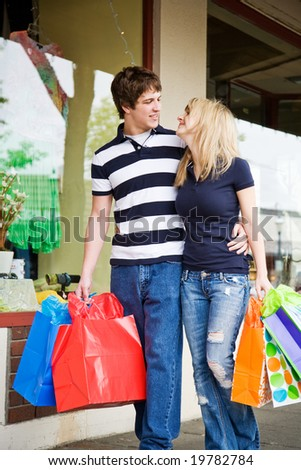 A caucasian couple carrying shopping bags walking in an outdoor mall - stock photo