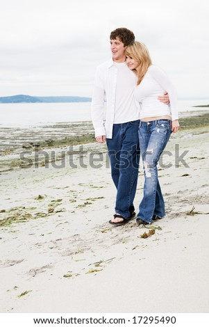 A caucasian couple in love walking on the beach - stock photo